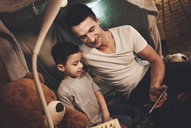Pai e filho estão assistindo filme no tablet à noite em casa