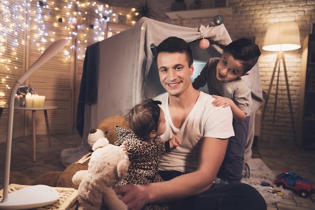 Pai e filho estão brincando com irmãzinha à noite.
