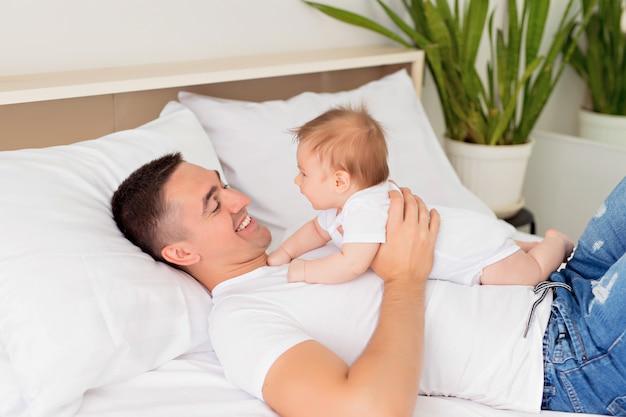 Pai e filho estão brincando em uma cama branca em um quarto ensolarado.