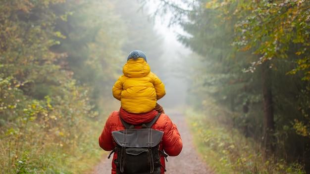 Pai e filho estão caminhando na floresta de outono na neblina