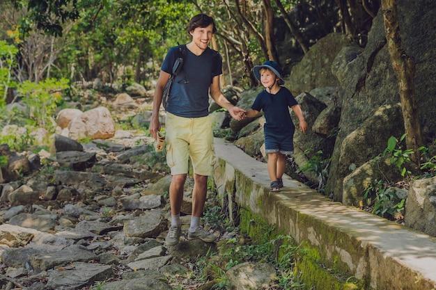 Pai e filho estão caminhando pela estrada da floresta
