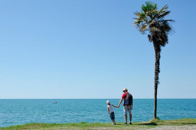 Pai e filho estão de costas com o mar e o céu azul