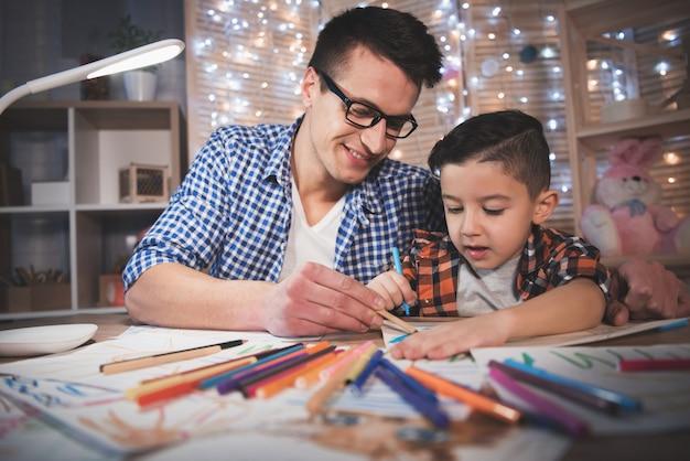 Pai e filho estão desenhando com lápis de cor.