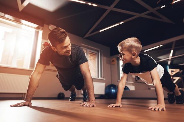 Pai e filho estão fazendo flexões no ginásio.