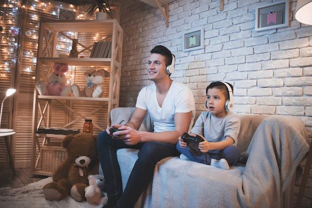 Pai e filho estão jogando videogames à noite em casa.