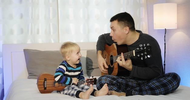 Pai e filho estão sentados na cama tocando violão. um garotinho loiro está segurando um ukulele
