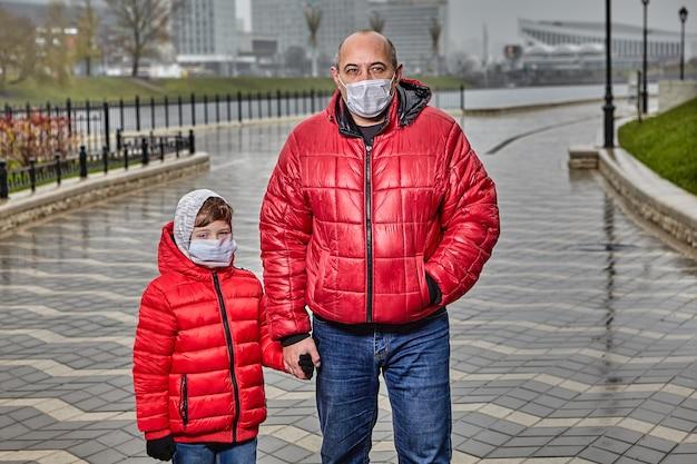 Pai e filho estão vestidos com roupas quentes para o frio e usam máscaras médicas de proteção em seus rostos durante uma epidemia de gripe ou poluição do ar.