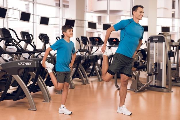Pai e filho esticam as pernas na academia.
