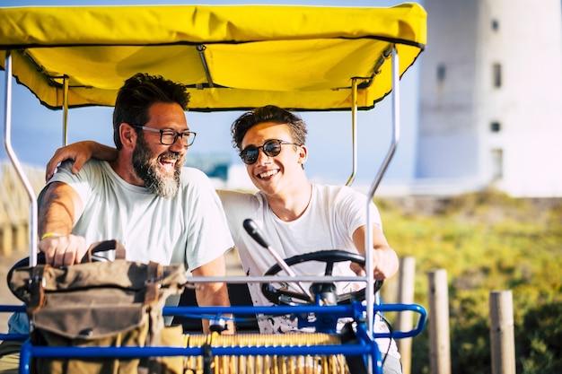 Pai e filho família juntos em uma bicicleta surrey se divertem em atividades de lazer ao ar livre ou férias de verão