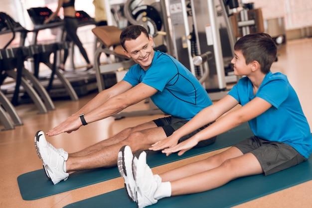 Pai e filho fazem alongamento no ginásio.