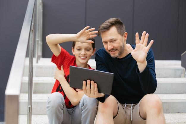 Pai e filho fazem videochamada usando um tablet na cidade em escada de concreto