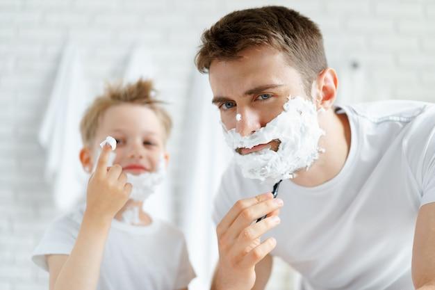Pai e filho fazendo a barba juntos no banheiro