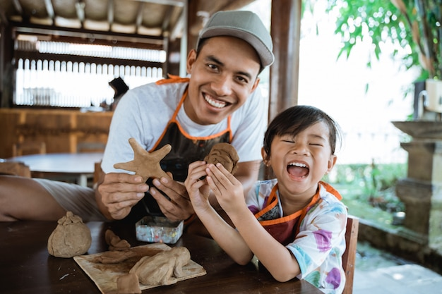 Pai e filho fazendo bens com argila