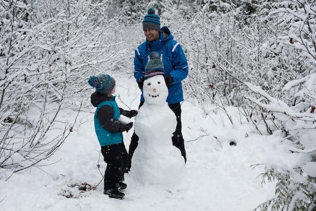Pai e filho fazendo boneco de neve
