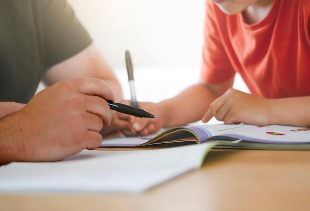 Pai e filho fazendo dever de casa juntos, professor ensinando menino a escrever.