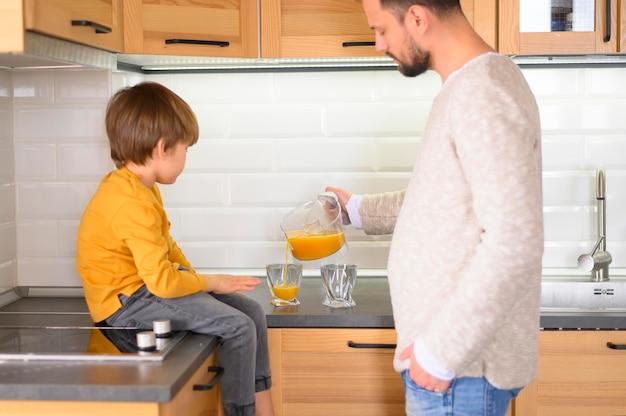 Pai e filho fazendo e bebendo suco de laranja