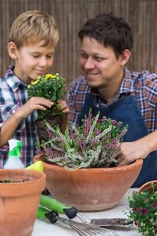 Pai e filho fazendo jardim urbano em casa. atividade que estimula a saúde mental e cerebral. plantar e cultivar flores de outono, passatempo ecológico e lazer, conceito de tempo para a família.