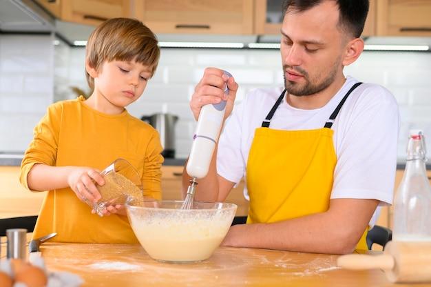 Pai e filho fazendo massa com a vista frontal do misturador