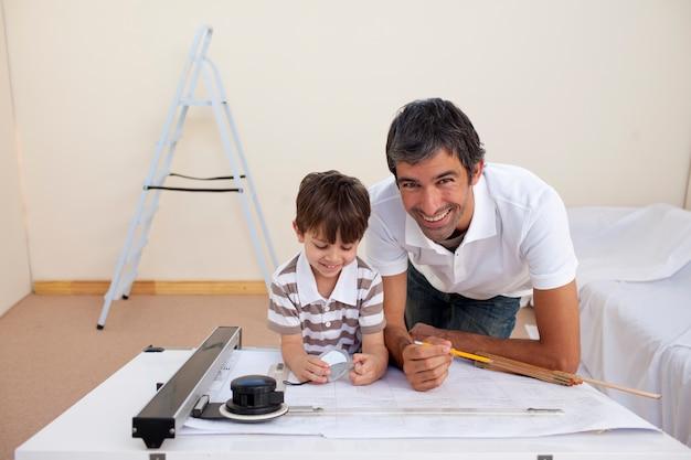 Pai e filho fazendo obras arquitetônicas no quarto