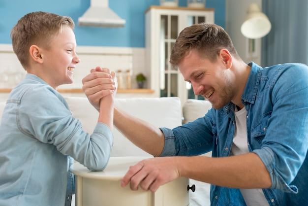 Pai e filho fazendo queda de braço dentro de casa