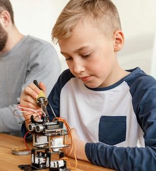 Pai e filho fazendo robô