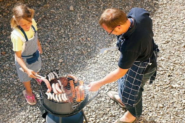 Pai e filho fazendo um churrasco