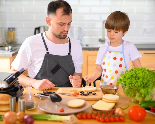 Pai e filho fazendo um hambúrguer