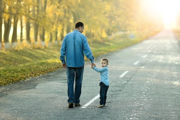 Pai e filho felizes caminhando em uma caminhada pela natureza em uma estrada no outono