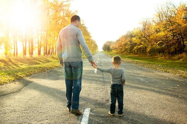 Pai e filho felizes caminhando na natureza no outono