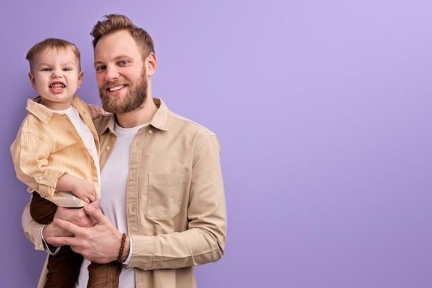Pai e filho felizes posando para a câmera sorrindo isolado na parede roxa