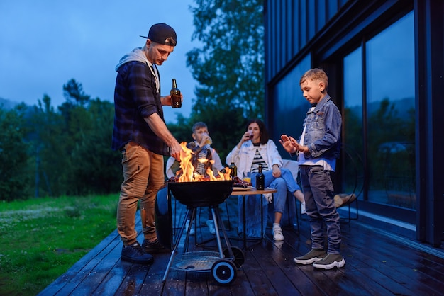Pai e filho felizes preparando um churrasco de férias em família no terraço de sua casa moderna e elegante