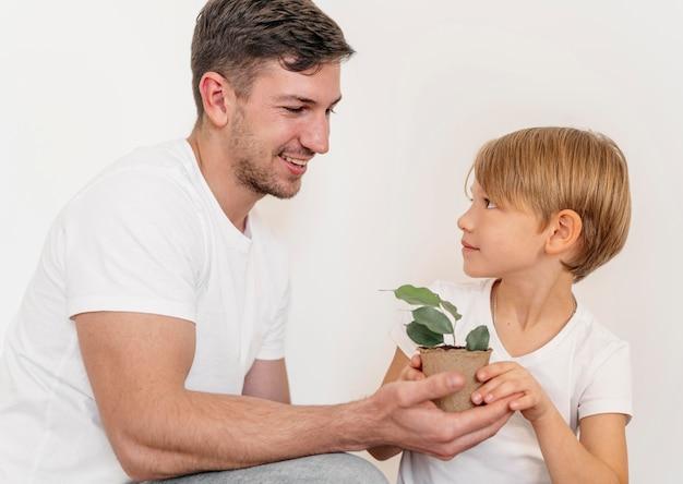 Pai e filho felizes segurando um vaso de planta