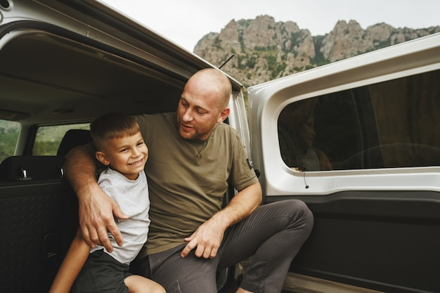 Pai e filho felizes sentados no porta-malas do carro