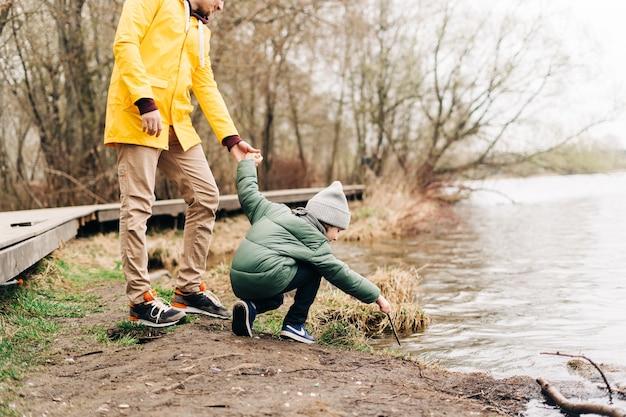 Pai e filho ficam na margem do lago brincando com água. família feliz com criança criança menino