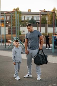 Pai e filho ficam no campo de esportes após o treino durante o pôr do sol. estilo de vida saudável.