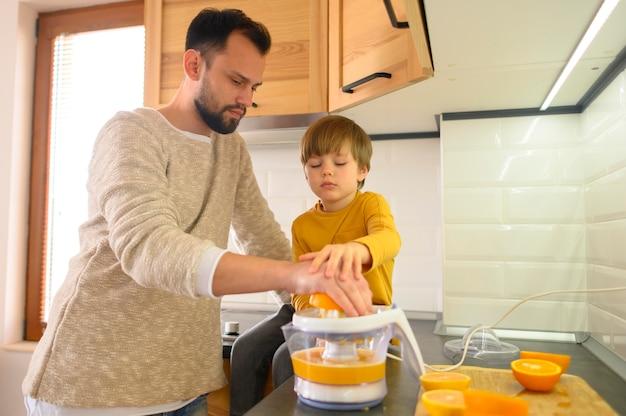 Pai e filho focados em fazer suco de laranja