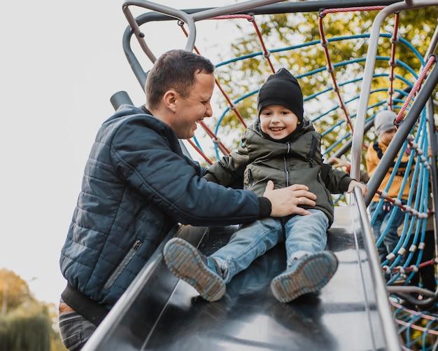 Pai e filho indo em um slide