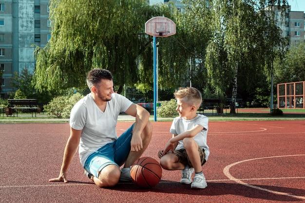 Pai e filho jogam basquete juntos na quadra de basquete