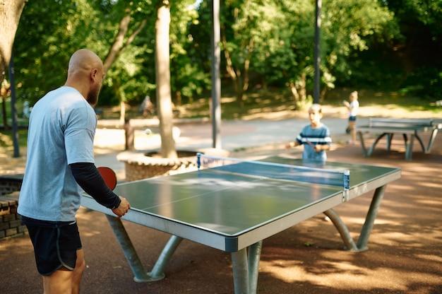 Pai e filho jogam tênis de mesa ao ar livre