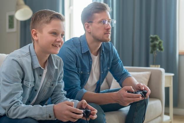 Pai e filho jogando videogame vista lateral