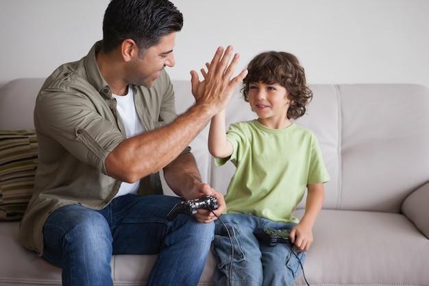 Pai e filho jogando videogames na sala de estar Foto Premium