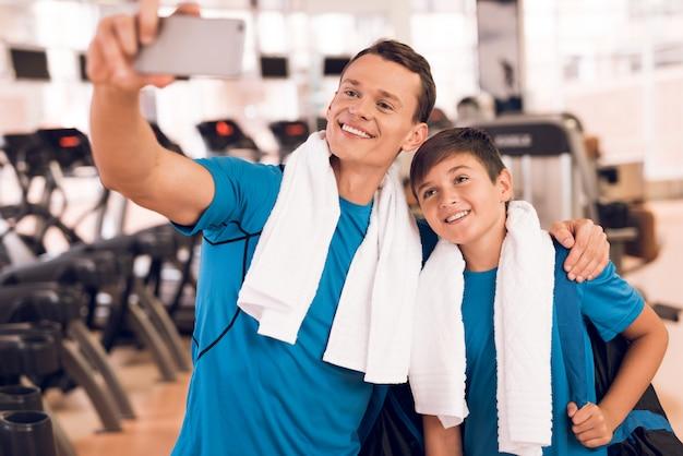 Pai, e, filho jovem, perto, esteiras rolantes, em, ginásio