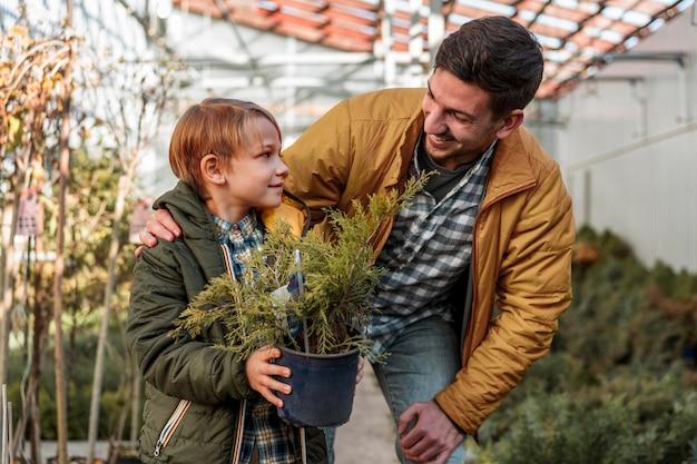 Pai e filho juntos comprando uma pequena árvore