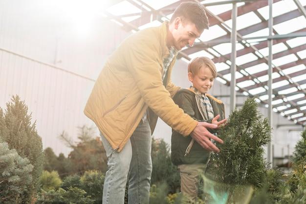 Pai e filho juntos em um viveiro de árvores olhando para a vegetação