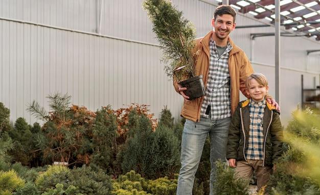 Pai e filho juntos em um viveiro de árvores posando com maconha