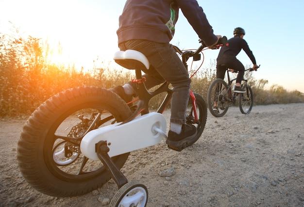 Pai e filho juntos estão andando de bicicleta pelo caminho no campo