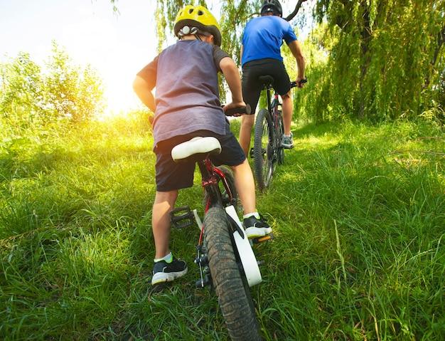 Pai e filho juntos estão andando de bicicleta pelo caminho