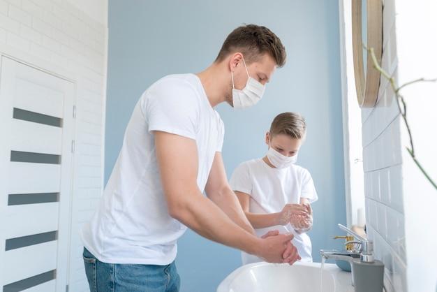 Pai e filho lavando as mãos na pia