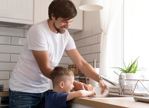 Pai e filho lavando louça