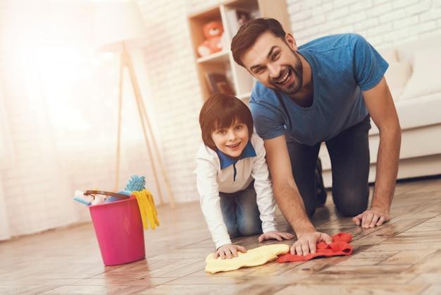 Pai e filho lavando o chão juntos.